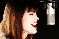 Young woman singing to the microphone in a studio. Face and microphone close-up - Young artist woman recording in a studio Royalty Free Stock Photography