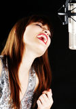 Young woman singing to the microphone in a studio Stock Images