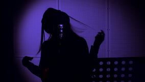 A young woman sings a song in a microphone in a recording studio under Neon light.  royalty free stock photography
