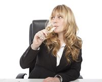 Young woman sipping champagne at her desk Stock Image