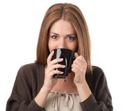 Young woman sipping from a cup Royalty Free Stock Photos