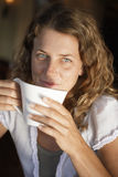 Young woman sipping cup of coffee in cafe, smiling, close-up, portrait Royalty Free Stock Images