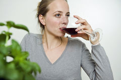 Young woman sipping red wine Royalty Free Stock Photos