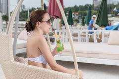 Young Woman Sipping Tropical Drink on Resort Patio Stock Photos