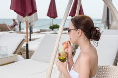 Young Woman Sipping Tropical Drink on Resort Patio Stock Images