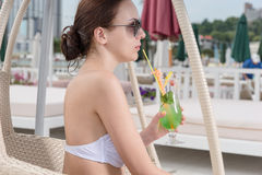 Young Woman Sipping Tropical Drink on Resort Patio Stock Image