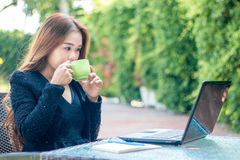 Young woman sips coffee. And is sitting with her laptop in the morning Stock Images