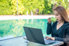 Young woman sips coffee. And is sitting with her laptop in the morning Royalty Free Stock Images