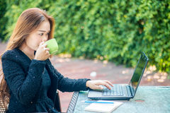 Young woman sips coffee. And is sitting with her laptop in the morning Royalty Free Stock Photography