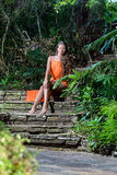 Young woman sirring in the tropical park Royalty Free Stock Photography