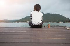 Young woman sit alone on wooden bridge has river, mountain, sky. Young asia woman sit alone on wooden bridge has river, mountain, sky are background. image for Stock Images