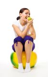 Young woman sit on ball with apple Stock Image