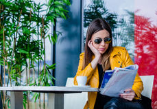 Young woman sit in cafe outdoor reading magazine. Urban girl with sunglasses sit in cafe outdoor reading  magazine  spring day city life concept Royalty Free Stock Photography