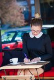 Young woman sit in cafe outdoor writes something in a notebook Stock Photography