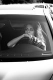 Young woman sit in car lean on steering wheel. Attractive young woman sit in car lean on steering wheel black an white stock photos