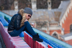 Young woman sit with cup coffee outdoor. The February stroll with a young woman Stock Image
