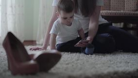 Young woman sit on the floor with a small baby boy and show him cartoon at mobile phone. Young woman sit on the floor with a small cute baby boy and show him stock video