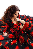 Young woman sit in gypsy black and red costume Royalty Free Stock Image