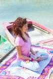 Young woman in a meditative yoga position sit on wooden pontoon on the lake hold magnolia flower. Young woman sit in a meditative yoga position on wooden pontoon stock images