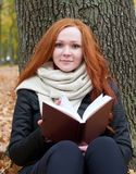 Young woman sit near tree in autumn park and read book, yellow leaves Royalty Free Stock Image