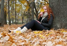 Young woman sit near tree in autumn park and read book, yellow leaves Stock Photo