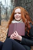 Young woman sit near tree in autumn park and read book, yellow leaves Stock Image