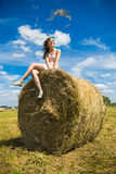 Young woman sit on a newly built hay stack. Royalty Free Stock Photos