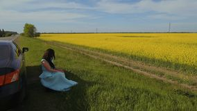 Young woman sit on roadside near her car and enjoy beautiful canola flower field stock video footage