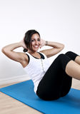 Young woman sit up. A young woman demonstrating a sit up or ab crunch exercise on a mat Stock Images