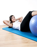 Young woman sit up with ball Stock Images