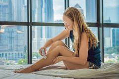 Young woman sitin on bed at home and doing epilation with epilator on legs. On the background of a window overlooking. The big city, skyscrapers stock photos