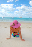 Young woman siting on a beach and looking to the h Stock Photography