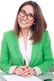 Young woman siting at a desk wearing a green jacket Royalty Free Stock Photography