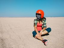 Young woman sits in the middle of desert wearing a helmet for buggy. Travel and sports concept. Young woman sits alone in the middle of the desert wearing a Royalty Free Stock Images