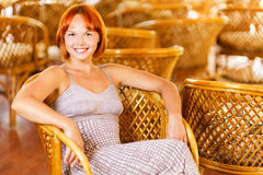 Young woman sits in armchair Stock Image