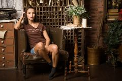 Young woman sits in an armchair Royalty Free Stock Photos