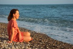 Young woman sits ashore of sea Royalty Free Stock Images