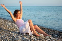 Young woman sits ashore of sea with rised hands Royalty Free Stock Image