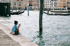 Young woman sits on the bank of Grand Canal browsing mobile phone. Stock Images