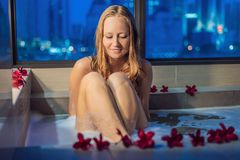 Young woman sits in a bath with foam and frangipani flowers agai. Nst the background of a panoramic window overlooking the skyscrapers and a big evening city Royalty Free Stock Photography