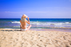 Young woman sits on the beach Stock Photo