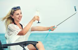 Young woman sits on the beach on a chaise longue, drinking wine and making photo against the background of the sea. Young woman sits on the beach stock photo