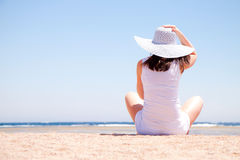 Young woman sits on the beach Stock Images