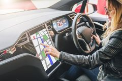 Woman sits behind wheel in car and uses electronic dashboard. Girl traveler looking for way through navigation system. stock photo