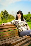 Young woman sits on a bench Stock Images