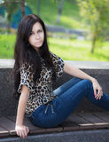 Young woman sits on a bench. Stock Photography