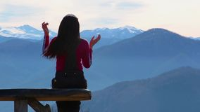 Young woman sits on bench outside and look at pictorial landscape with mountains stock video footage