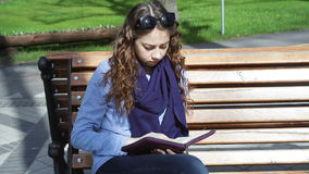 Young woman sits on a bench in the Park and reading book.  stock footage
