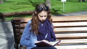 Young woman sits on a bench in the Park and reading book stock video footage