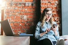 Young woman sits in cafe on windowsill and uses smartphone. Hipster girl checking e-mail, chatting, blogging, working. Young woman sits in cafe on windowsill royalty free stock image